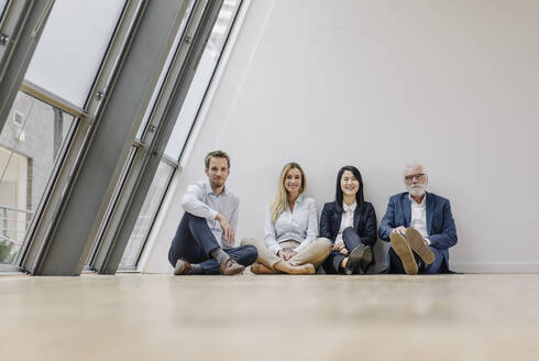 Portrait of smiling business people sitting on the floor in office - JOSF03930