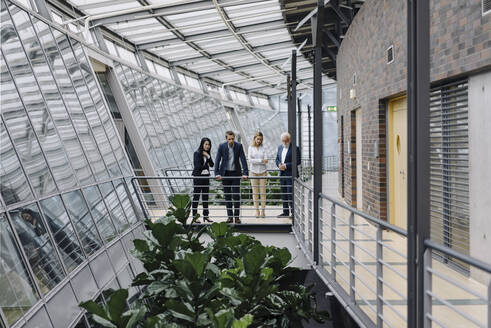 Business people standing on skywalk in modern office building - JOSF03939