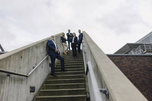 Business people standing on exterior stair looking out - JOSF03945