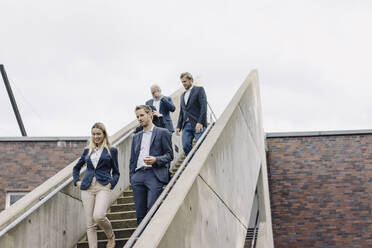 Business people walking down exterior stair - JOSF03948