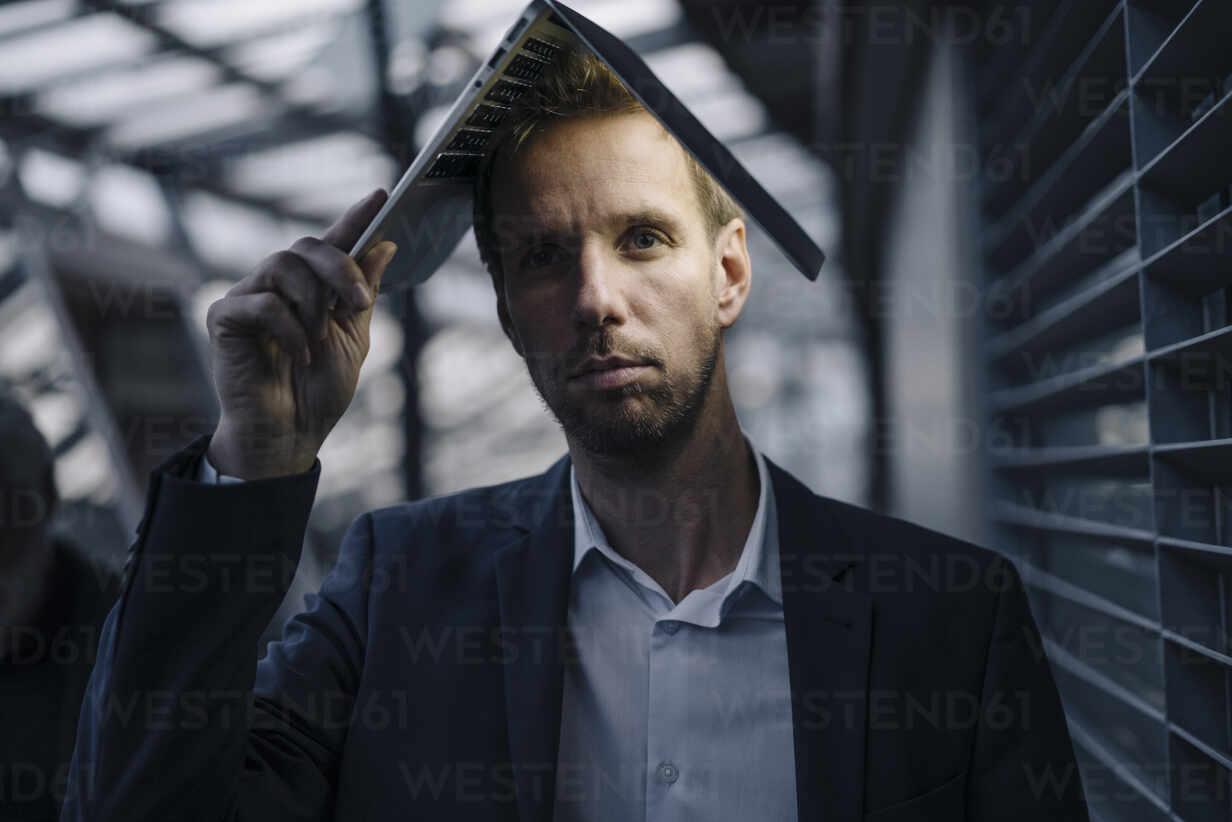 Businessman in office holding illuminated laptop above his head - JOSF03969 - Joseffson/Westend61