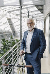 Portrait of a senior businessman with a bike in a modern office building - JOSF03978
