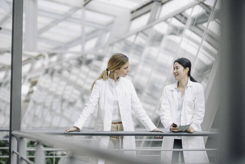 Two female doctors talking in a modern building - JOSF03996