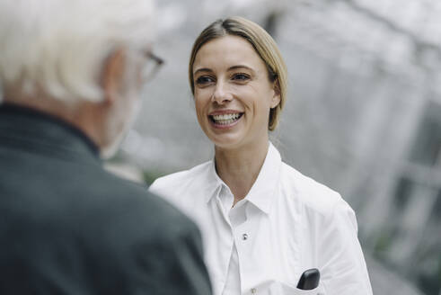 Smiling female doctor talking to senior man - JOSF04005
