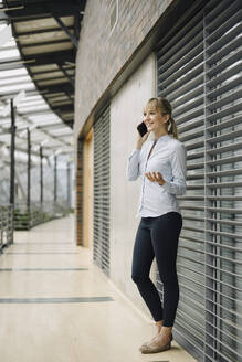 Smiling young businesswoman on the phone in a modern office building - JOSF04014