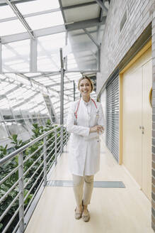 Portrait of a smiling female doctor on a passageway - JOSF04020