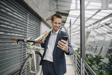 Smiling businessman with cell phone carrying bicycle in modern office building - JOSF04032
