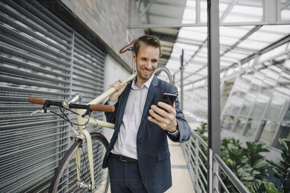 Smiling businessman with cell phone carrying bicycle in modern office building - JOSF04032 - Joseffson/Westend61