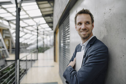 Smiling businessman leaning against a wall in modern office building - JOSF04038