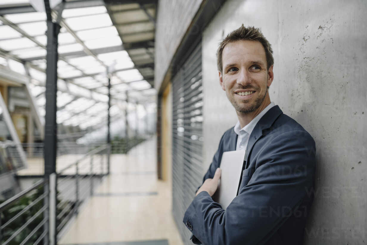Smiling businessman leaning against a wall in modern office building - JOSF04038 - Joseffson/Westend61
