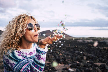 Blond woman blowing confetti in the air, Tenerife, Spain - SIPF02096