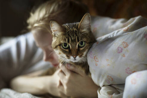 Woman embracing cat while lying on bed at home - CAVF70050