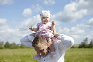 Portrait of cute baby girl sitting on father's shoulder at field against sky during sunny day - CAVF70053