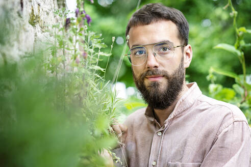 Portrait of young bearded man, standing in garden - PESF01734