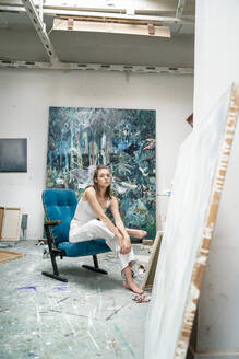 Young artist sitting in her studio - PESF01758
