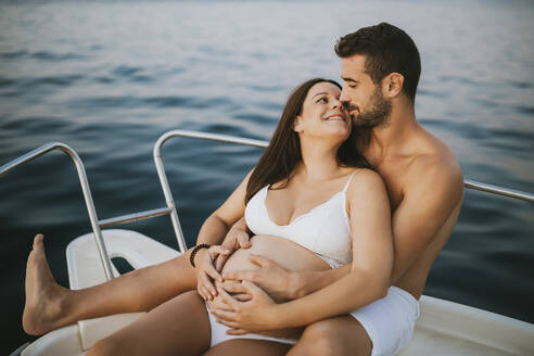 Romantic couple with pregnat woman sitting on boat - MIMFF00023