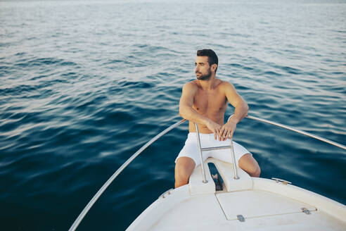 Young man sitting at bow of a boat, watching the sea - MIMFF00026