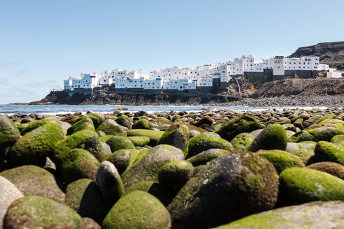 View of white house neighborhood facing the sea from a pebble beach - CAVF70333