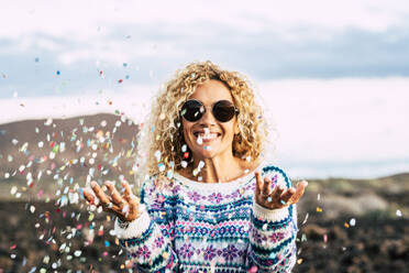 Portrait of happy blond woman celebrating with confetti, Tenerife, Spain - SIPF02099