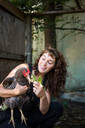 Happy woman feeding leaves to hen while crouching in poultry farm - CAVF70371