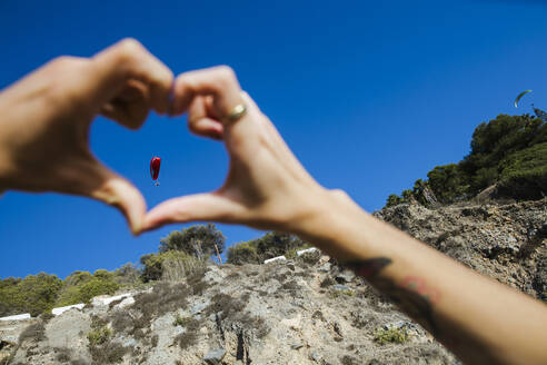 Young man forming heart shape with his fingers, paraglider - LJF01086