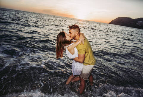 Young couple kissing each other at the beach during sunset - LJF01098