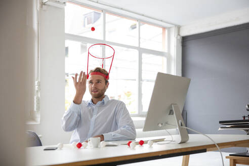 Young businessman in his office, throwing a ball in a hoop - MOEF02695