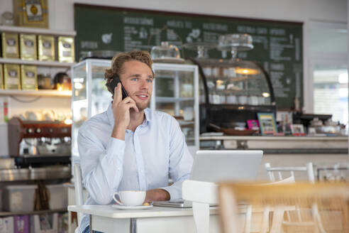 Young businessman phoning in a cafe - MOEF02701