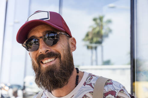 Smiling mature man with beard, red basecap and sunglasses - TCF06212