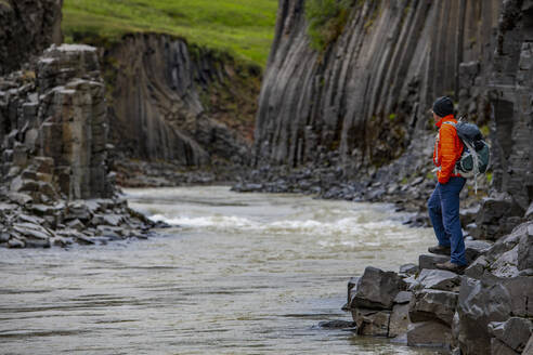 Hiker admiring basalt cliffs in Stulagil Canyon, Jokuldalur, Iceland - CUF53619