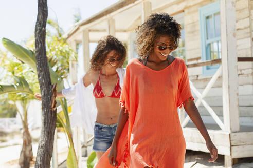 Young women friends outside sunny beach hut - HOXF04521