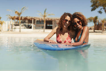 Portrait happy young women friends with surfboard in sunny ocean - HOXF04548