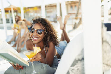 Portrait happy, carefree young woman reading book and drinking cocktail on beach - HOXF04563