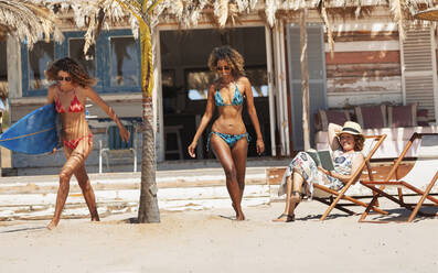 Young women in bikinis with surfboard on sunny beach - HOXF04569