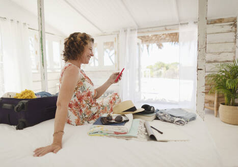 Woman with smart phone unpacking suitcase on beach hut bed - HOXF04572
