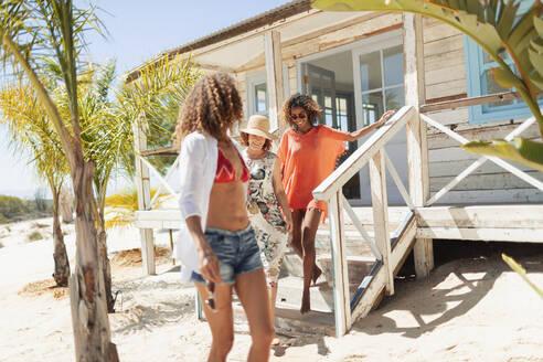 Women descending sunny beach hut steps - HOXF04581