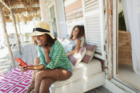 Young woman with smart phone relaxing on beach hut patio - HOXF04596