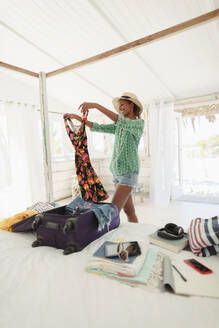 Happy woman unpacking suitcase in beach house bedroom - HOXF04599