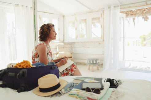 Serene woman writing in journal next to suitcase in beach hut bedroom - HOXF04608