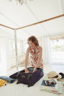Woman unpacking suitcase in beach hut bedroom - HOXF04620