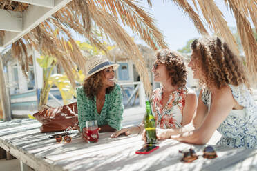 Women friends drinking cocktail and beer and sunny beach bar - HOXF04629