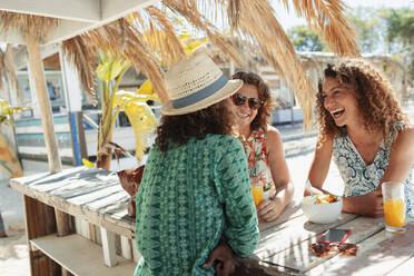 Happy women eating breakfast at sunny beach bar - HOXF04632