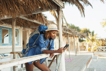Young female backpacker using smart phone on beach hut patio - HOXF04635