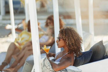 Young woman relaxing with cocktail on beach patio - HOXF04644
