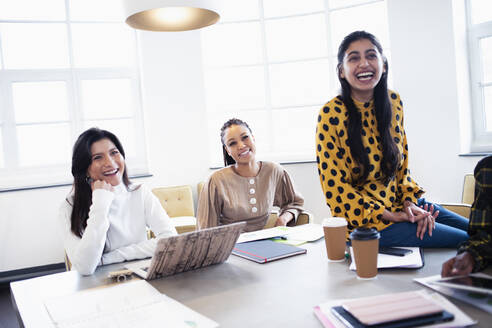Businesswomen laughing in conference room meeting - HOXF04836
