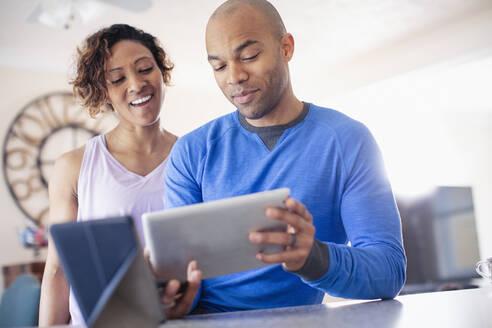 Couple using digital tablet - HOXF04860