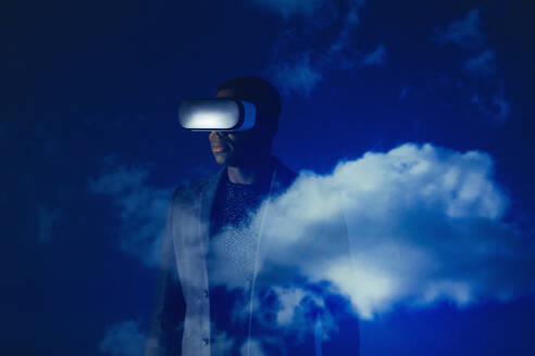 Double exposure businessman with virtual reality simulator glasses against blue sky with clouds - CAIF23394