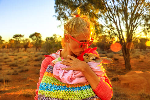 Tourist woman holding and kissing kangaroo joey at sunset light in Australian Outback, Red Center, Northern Territory, Australia, Pacific - RHPLF13206