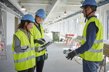 Smiling male and female architects discussing over digital tablet at construction site - MASF15249