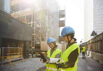 Female engineers discussing over digital tablet at construction site during sunny day - MASF15270